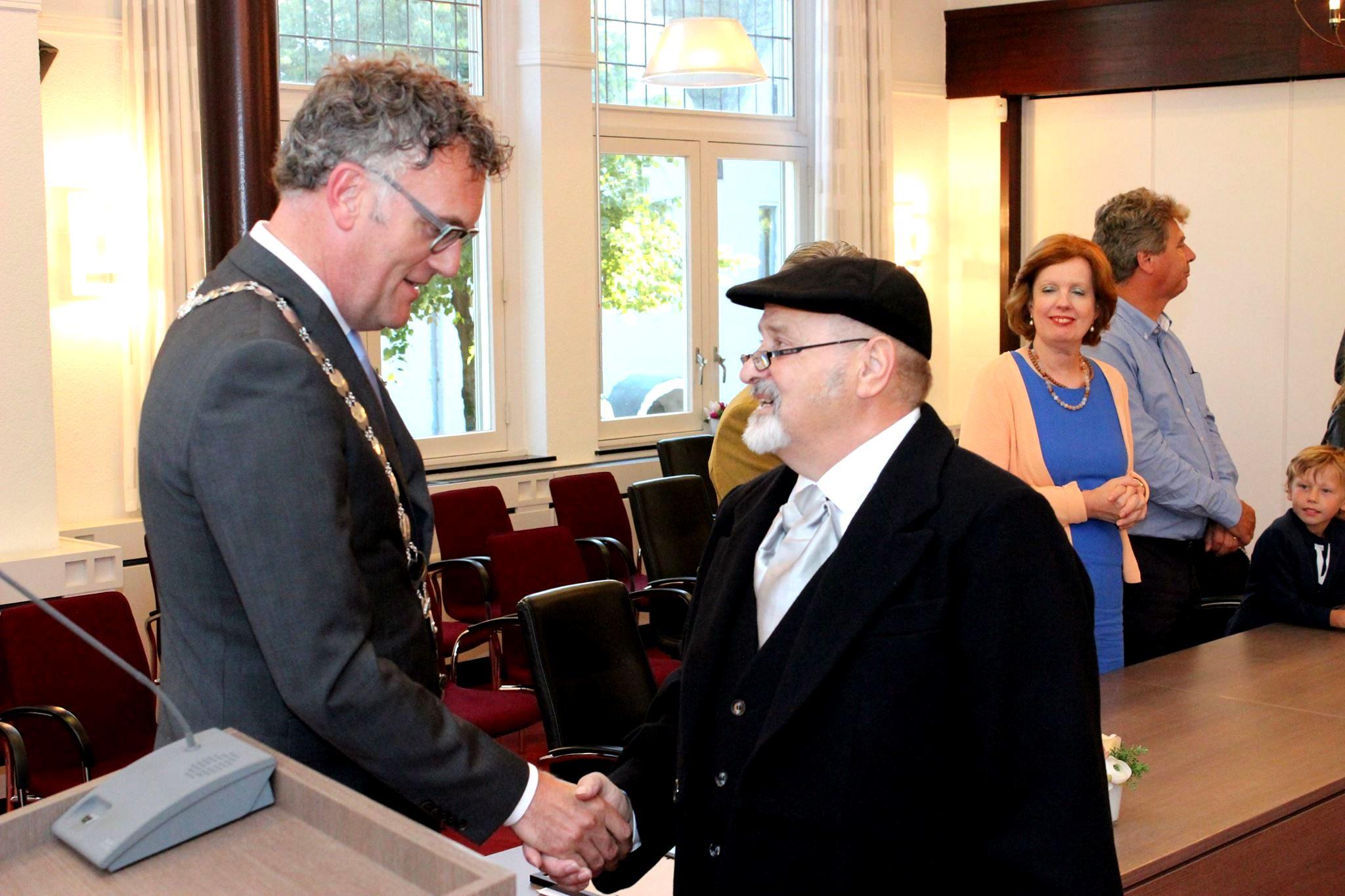 Burgemeester Hans Janssen feliciteert Henk van den Nieuwenhuizen alias 'Hein de Roeper'
