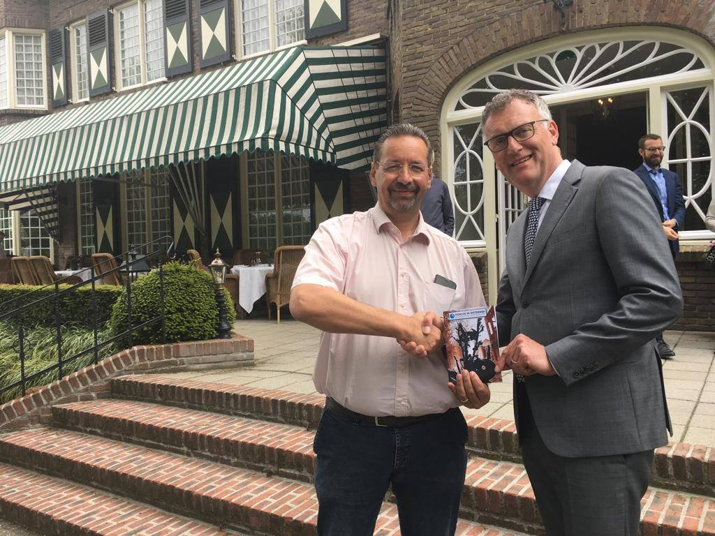"""Burgemeester Hans Janssen neemt het eerste boekje van de nieuwe wandelroute """"Oorlog in Oisterwijk"""" in ontvangst."""